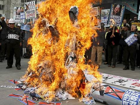 Mielenosoittajat polttivat Pohjois-Korean johtajien kuvia Soulissa maanantaina.