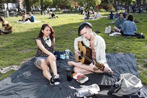 Ystävykset Sara Sanchez (vas.) ja Josiah Hixon viettivät sunnuntaita puistossa. Hixon on karanteenin aikana harjoitellut kitaransoittoa.