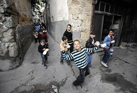 Syyrialaiskoululaiset leikkivät kujalla Damaskoksessa viime lauantaina.