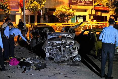 Poliisi tutkii autopommi-iskussa tuhoutunutta autoa Islamabadissa lauantaiaamuna.