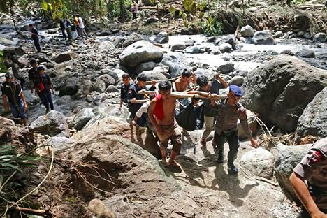 Pelastustyöntekijät kantoivat hyökytulvan uhrin ruumista Sibolangitissa, Pohjois-Sumatralla.