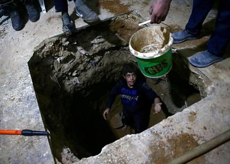 Mies kaivoi suojatilaa talon alle saarretussa Itä-Ghoutassa keskiviikkona.