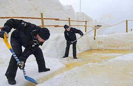 Pekka Ovasta ja Jari Huotari tekivät puroja sulamisvesille Kemin lumilinnassa keskiviikkona. Se on tarkkailussa lauhojen kelien vuoksi.