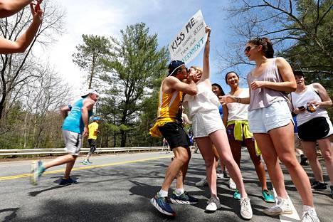 21-vuotias Courtney Peterson kannustaa Bostonin maratonin osallistujia maanantaina tarjoamalla heille suukkoja. Hänen kyltissään kehutaan juoksijoiden suorituksia paremmiksi kuin hallituksen.
