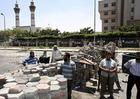 Tuhannet kairolaiset Muslimiveljeskunnan kannattajat uhmaavat sisäministerin määräystä purkaa protestileiri Rabaa al-Adawian kaupunginosassa. Suojakseen islamistit ovat rakentaneet katukivistä moninkaertaisia barrikadeja.