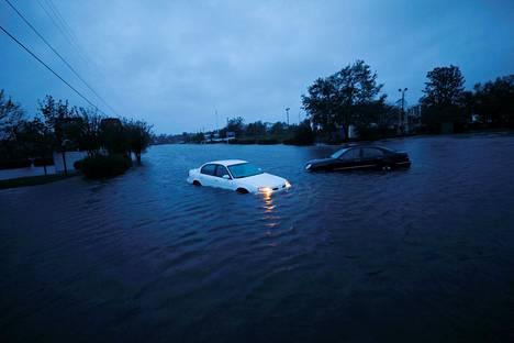 Hylätty auto seisoi hätävilkut päällä tulvaveden valtaamalla kadulla Wilmingtonissa Pohjois-Carolinassa lauantaia-aamuna.