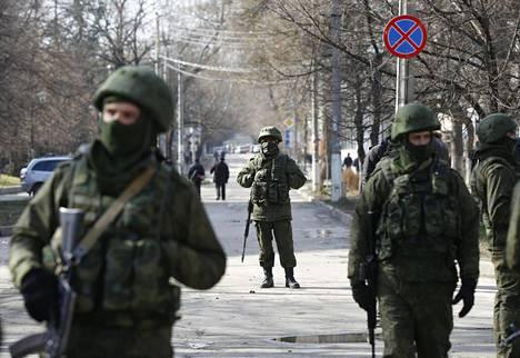 Aseistetut miehet partioivat alueparlamentin rakennuksella Simferopolissa Krimillä maaliskuussa 2014.