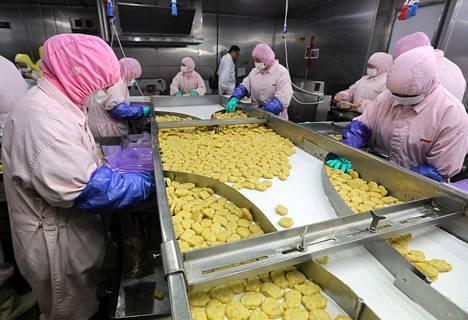 Työntekijät valmistamassa ruokaa Shanghai Husi Food Co:n tehtaassa heinäkuun 20. päivänä.