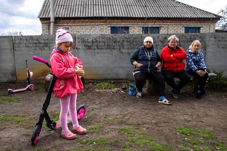 Viisivuotias Karolina ajelee potkulaudallaan Zoloten kuoppaisella kylänraitilla. Tanja (vas.), Natalija Viktorovna ja Inna Anatoljevna istuskelivat kylänraitilla Zolotessa, jossa asuu paljon Itä-Ukrainan separistialueilta lähteneitä evakkoja.