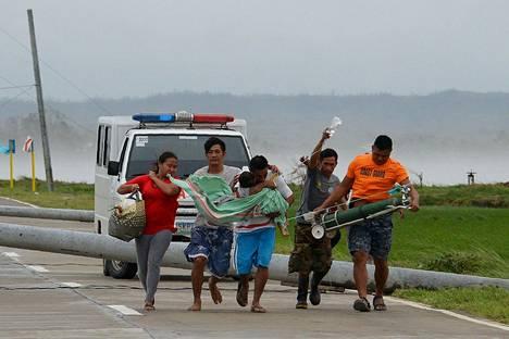 Perheenjäsenet kantoivat sairasta lastaan eteenpäin juosten filippiiniläisessä Baggaon kaupungissa, kun ambulanssi oli jäänyt jumiin tielle kaatuneiden sähköpylväiden väliin lauantaina.