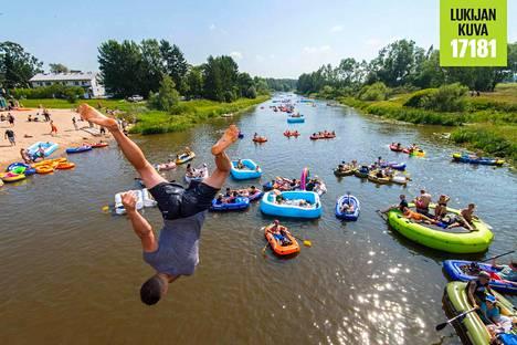 Ihmiset hyppivät kaljakellujien sekaan Vantaanjokeen Tapaninvainion uimarannan lähellä lauantaina.