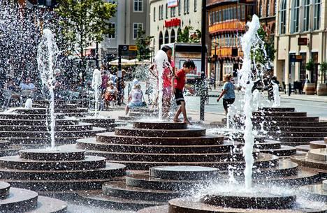 Ihmiset hakivat suihkulähteestä helpotusta kuumuuteen keskiviikkona Tanskan Ålborgissa.
