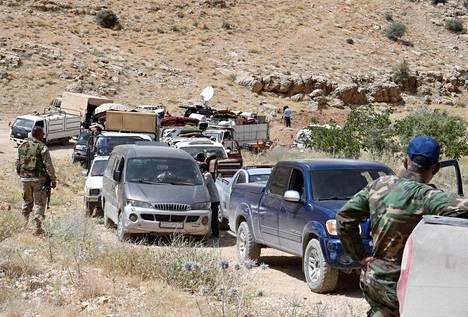 Hizbollahin jäsenet saattavat syyrialaisia pakolaisia kohti Arsalin kaupunkia Libanonissa.