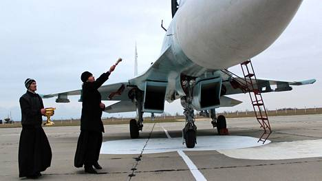 Venäläinen ortodoksipappi siunasi SU-27 SM -hävittäjää Krimin sotilaallisella lentokentällä marraskuussa 2014.