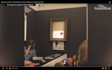 Banksyn maalaus Tyttö ja ilmapallo tuhoutui itsekseen Sotheby'sin taidehuutokaupassa. Kuva on The Guardianin julkaisemasta videosta.