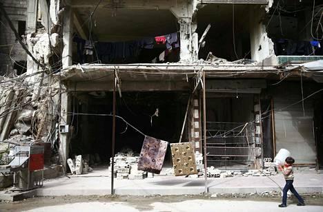 Syyrialaispoika kantoi kanisteria pommitetussa Itä-Ghoutassa torstaina.