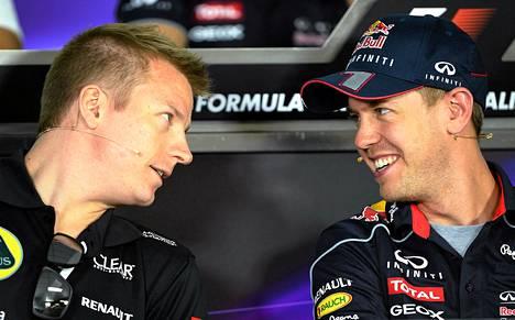 Kimi Räikkönen (vas) vaihtoi ajatuksia Saksan Sebastian Vettelin kanssa ennen F1-autojen Australian osakilpailun harjoituksia torstaina.