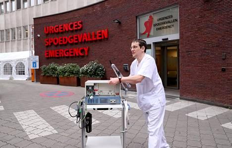 Sairaanhoitaja hengityslaitteen kanssa Saint-Jeanin sairaalan edustalla Belgiassa perjantaina.