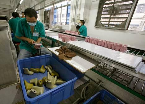 Mies valmisti lastenkenkiä kenkätehtaassa Dongguanissa kesäkuussa 2009.