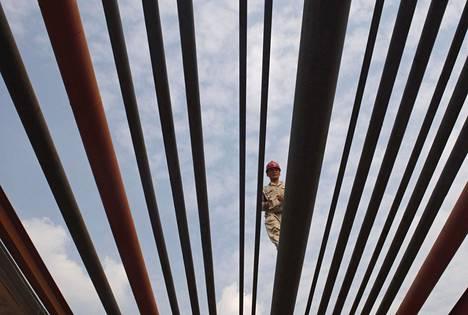 Öljynjalostamon työntekijä kävelee öljyputkia pitkin Sichuanissa. Kiina on yksi halvasta öljystä hyötyvistä maista, mutta rakennemuutokseen pyrkivä maa ei investoi enää entiseen tahtiin.