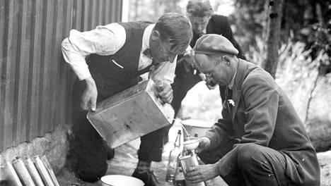 "Ralf Roos (vas.), Lars Gustav Sonck ja Fjalar Sonck jakavat pirtua kanisterista puolen litran ""lahnoihin"" Santahaminassa 1920-luvulla."