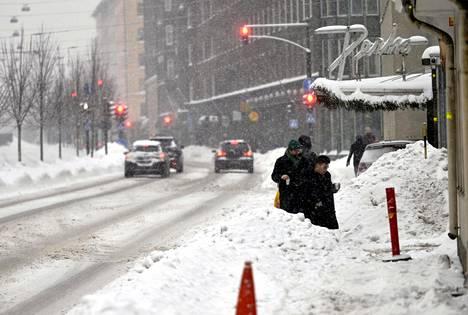 Autoilijoita ja jalankulkijoita liikenteessä keskiviikkoisessa lumisateessa Helsingissä.