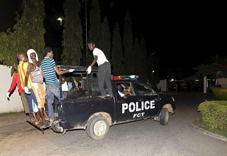 Vapaaehtoiset matkustivat poliisiauton kyydillä auttamaan pommi-iskun uhreja Abujassa perjantain vastaisena yönä.