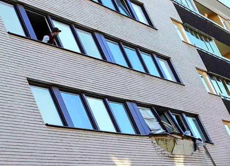 Asukas katseli räjähdyksen naapuriasunnolle aiheuttamia vaurioita Sundbybergissä Tukholman lähellä perjantaina.