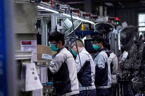 Työntekijöitä autonistuimia valmistavan tehtaan kokoonpanolinjalla Shanghaissa maanantaina.