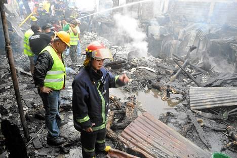 Palomiehet tutkivat onnettomuuspaikkaa Manilan slummissa lauantaina.