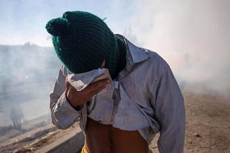 Siirtolainen pyrki suojautumaan kyynelkaasulta Tijuanassa sunnuntaina.