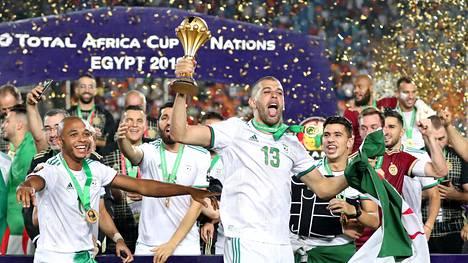 Algerian Islam Slimani pitelee palkintoa muun joukkueen juhliessa mestaruutta taustalla.