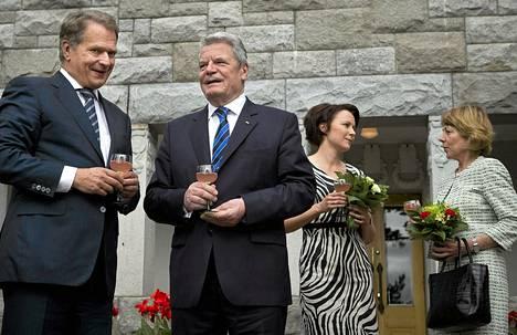 Presidentti Sauli Niinistö vinkasi Saksan presidentti Joachim Gauckille kun samaan aikaan presidenttien puolisot Jenni Haukio ja Daniela Schadt (oik.) keskustelivat taustalla Kultarannassa lauantaina.