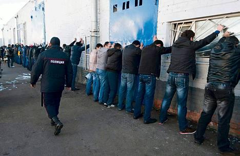 Poliisi pidätti siirtotyöläisiä Birjuljovon kaupunginosan vihannestorilla Moskovassa maanantaina.