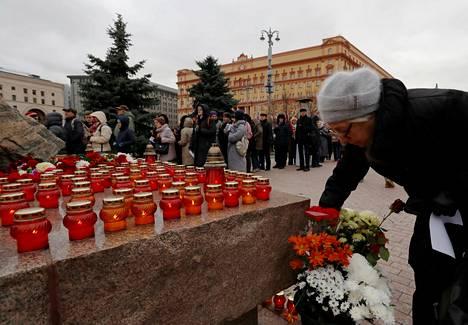 Venäläisnainen asetteli kynttilää maanantaina Solovetskin kivelle Lubjankan aukiolla Moskovan keskustassa, jossa luettiin Stalinin vainojen uhrien nimiä. Muistomerkin takana ihmiset jonottavat vuoroaan. Taustalla salaisen poliisin FSB:n päämaja.