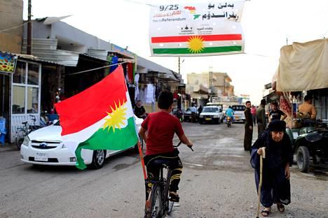 Kurdipoika pyöräili sunnuntaina Kurdistanin lipun kanssa Kirkukin eteläpuolella sijaitsevassa Tuz Khurman kaupungissa.