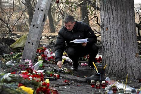 Rikostekninen tutkija katsoi kuolleiden mielenosoittajien muistokukkia lähellä Kiovan Itsenäisyydenaukiota keskiviikkona.