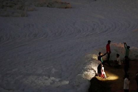 Ihmiset ottavat selfieitä saasteista vaahtoavan Yamuna-joen rannalla Delhissä Intiassa.