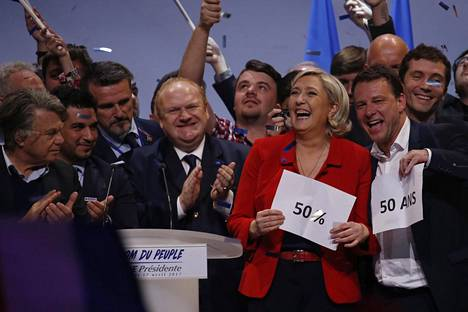 Marine Le Pen riemuitsee tukijoukkojensa kanssa Pariisissa järjestetyssä vaalitilaisuudessa.