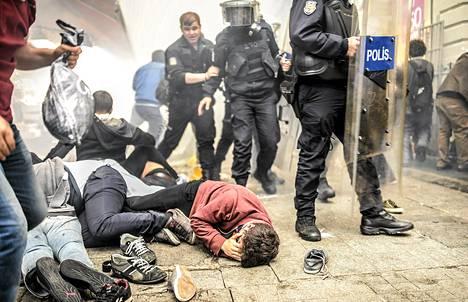 Loukkaantuneita mielenosoittajia makaa maassa poliisien ammuttua heitä kyynelkaasulla Istanbulissa lauantaina.