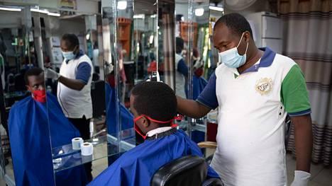 Ruandalainen parturi tekee työtään maski kasvoillaan toukokuun alussa, kun koronan takia suljettu maa avattiin jälleen. Ruandan presidentti on arvioinut, että joillakin Afrikan mailla voi mennä sukupolvi tai enemmän pandemian aiheuttamasta taloudellisesta šokista toipumiseen.