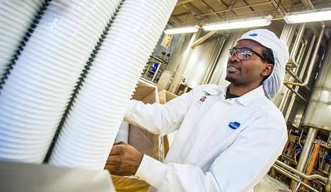 """John Chege Kiguru hoitaa rahkan pakkauskonetta Valion tehtaalla Seinäjoella. Hänelle itselleenkin rahka maistuu, vaikka hän on kotoisin Keniasta, jossa sitä ei tunneta. """"Meillä on muita maitotuotteita, juustoa ja hapatettua maitoa."""""""