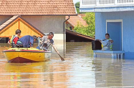 Mies odotti pelastajien saapumista talonsa edustalla maanantaina Vojskovan kylässä Bosnia ja Hertsegovinassa.