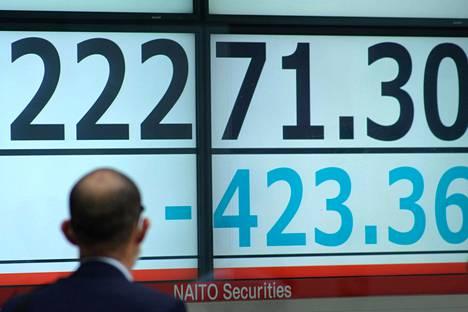 Mies seurasi pörssikurssien laskua osoittavaa lukua Tokion pörssissä maanantaina.