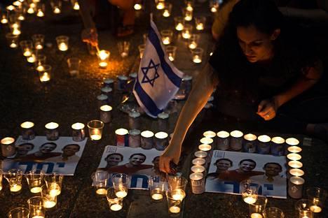 Israelilaisnainen sytytti kynttilän kolmen surmatun pojan muistoksi järjestetyssä mielenosituksessa Tel Avivissa kesäkuun lopulla Israelissa.