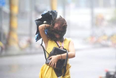 Kiinalaisnainen yritti edetä myrskyssä kymmenen miljoonan asukkaan rannikkokaupunki Shenzhenissä sunnuntaina.