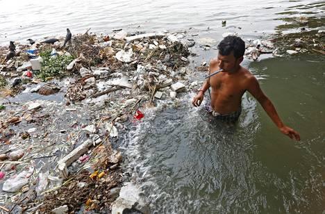 Mies kylpee hammasharja suussaan roskien seassa Ganges-virrassa Kalkutassa tiistaina.