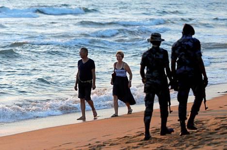 Turistit kävelivät rannalla Colombossa heinäkuun lopussa. Aseistetut sotilaat partioivat vieressä.