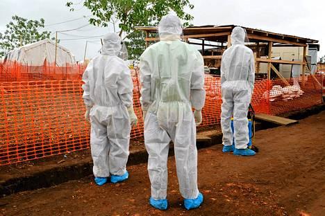 Sierra Leonen terveysministeriön työntekijöitä suojapuvuissa ebolaklinikan ulkopuolella Kailahussa.