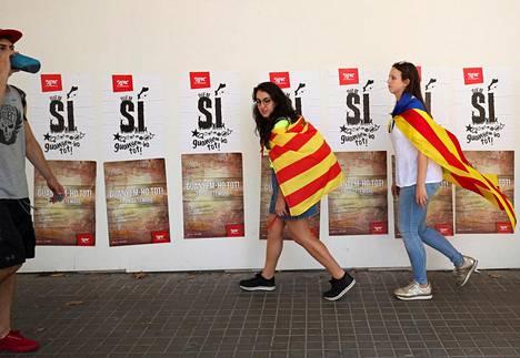 Itsenäisyyden kannattajat kävelivät kampanjajulisteiden ohi Barcelonassa Katalonian kansallispäivänä maanantaina. Aluehallituksessa istuvan Katalonian tasavaltalaisen vasemmiston (ERC) nuorisojärjestön julisteissa on kuvattu karttana koko katalaaninkielinen alue, joka kattaa Katalonian lisäksi Valencian ja Baleaarien itsehallintoalueet, Andorran sekä siivun Etelä-Ranskasta.